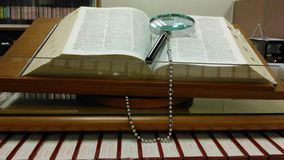 Magnifying glass and encyclopedia. In the library royalty free stock photo