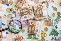 Magnifying glass and euro banknotes Stock Image