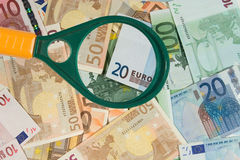 Magnifying glass and euro bills Royalty Free Stock Photos