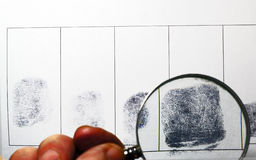 Magnifying glass examine fingerprints. Royalty Free Stock Photo