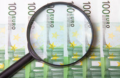Magnifying glass on few hundred euro banknotes Stock Image