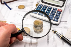 Magnifying glass with financial documents, coin, notepad, calculato Stock Photo
