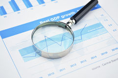 Magnifying glass on financial graph, accounting background Stock Image