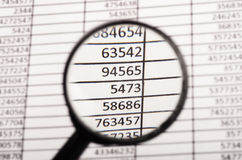 Magnifying glass and financial report Royalty Free Stock Photos
