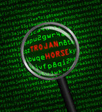 Magnifying glass finds trojan horse in computer code Stock Photos