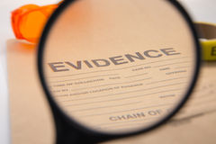 Magnifying glass focus on evidence bag Stock Photos