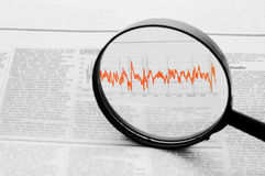 A magnifying glass focusing on a graph. In the business section of the newspape royalty free stock images