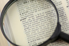 Magnifying glass focusing on profit word Stock Photos