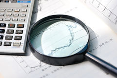A magnifying glass focusing on stock chart Stock Image