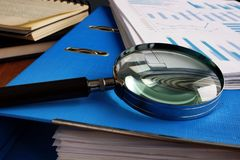 Magnifying glass and folder with pile of business documents.  stock photography