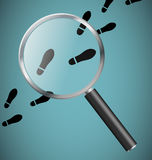 Magnifying glass and footprints Royalty Free Stock Photos