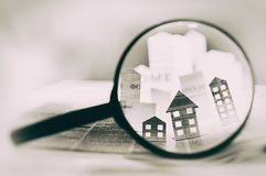 Magnifying glass in front of an open newspaper with paper houses. Concept of rent, search, purchase real estate royalty free stock image