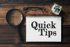 Magnifying glass, glasses, cactus and notebook with QUICK TIPS word on wooden table stock image