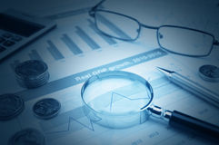 Magnifying glass, glasses, calculator, pen, and coin on financia Royalty Free Stock Image