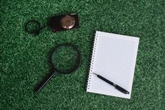 Magnifying glass, green plant and blank notebook on a green grass stock images