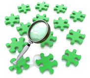 Magnifying glass on the green puzzle Royalty Free Stock Photo