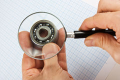 Magnifying glass  in hand and  bearing Royalty Free Stock Images