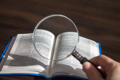 Magnifying glass in hand, and book 2 Royalty Free Stock Photo