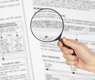 Magnifying glass in hand and business text Stock Photography