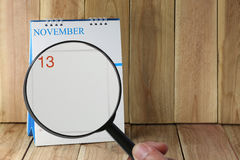 Magnifying glass in hand on calendar you can look Day Thirteen o Royalty Free Stock Photos