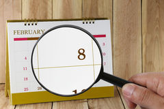 Magnifying glass in hand on calendar you can look Eighth day  Royalty Free Stock Images