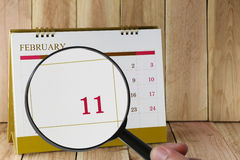 Magnifying glass in hand on calendar you can look eleven day of Stock Image