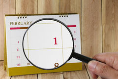 Magnifying glass in hand on calendar you can look first day of m Stock Photo