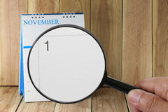 Magnifying glass in hand on calendar you can look first day of m Stock Image