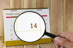 Magnifying glass in hand on calendar you can look fourteenth day Stock Photos