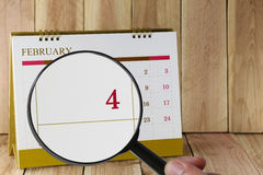 Magnifying glass in hand on calendar you can look fourth day of Stock Photos