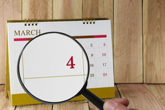 Magnifying glass in hand on calendar you can look fourth day of Stock Images