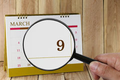 Magnifying glass in hand on calendar you can look ninth day of m Stock Photo
