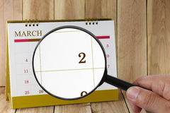 Magnifying glass in hand on calendar you can look second day of Royalty Free Stock Photo