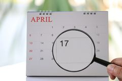 Magnifying glass in hand on calendar you can look seventeenth da. Y of month,Focus number seventeen in April,Concept in business and meetings Royalty Free Stock Photography