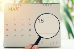 Magnifying glass in hand on calendar you can look Sixteen day of. Month,Focus number sixteen in May,Concept in business and meetings Stock Photos
