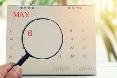 Magnifying glass in hand on calendar you can look Sixth day of m. Onth,Focus number one in May,Concept in business and meetings stock photo