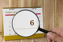 Magnifying glass in hand on calendar you can look Sixth day  Stock Image