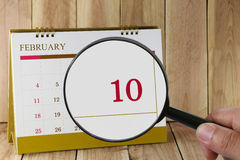 Magnifying glass in hand on calendar you can look tenth day  Royalty Free Stock Photos
