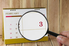 Magnifying glass in hand on calendar you can look third day of m Stock Images