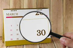 Magnifying glass in hand on calendar you can look Thirty day of Stock Images