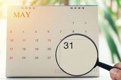 Magnifying glass in hand on calendar you can look Thirty one day. Of month,Focus number thirty in May,Concept in business and meetings royalty free stock images