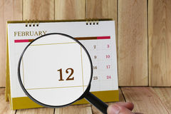 Magnifying glass in hand on calendar you can look twelfth day of. Month,Focus number twelve in February,Concept in business and meetings Royalty Free Stock Photography
