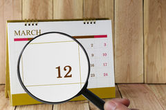 Magnifying glass in hand on calendar you can look twelfth day of Royalty Free Stock Photos