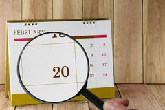 Magnifying glass in hand on calendar you can look Twentieth day Stock Images
