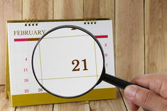 Magnifying glass in hand on calendar you can look Twentieth one Stock Photos