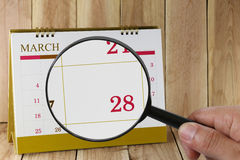 Magnifying glass in hand on calendar you can look Twenty-eight d Stock Photos