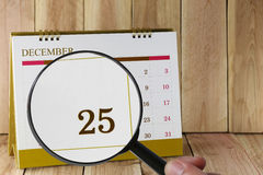 Magnifying glass in hand on calendar you can look Twenty Five da. Te of month,Focus number Twenty Five in December,Concept in business and meetings stock photography
