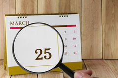 Magnifying glass in hand on calendar you can look Twenty Five da Royalty Free Stock Photo