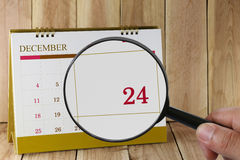 Magnifying glass in hand on calendar you can look Twenty-four da. Te of month,Focus number Twenty-four in December,Concept in business and meetings stock photo