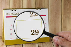 Magnifying glass in hand on calendar you can look Twenty-nine da Royalty Free Stock Images
